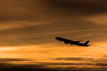 Silhouette airplane in the sunset sky
