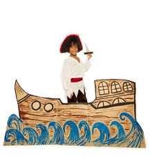Black boy in costume of pirate on cardboard ship