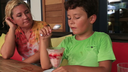 Child eating ice cream at the restaurant with his mother