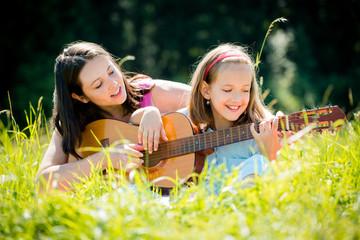 Mother teaching daughter playing guitar