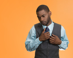 Shy, coy, sad young handsome business man, orange background
