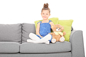 Cute little girl sitting on couch with teddy bear
