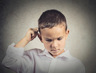 Thinking sad child, scratching back of his head, grey background