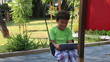 child swinging and using digital tablet in playground