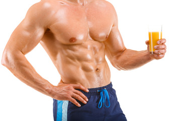 Healthy muscular man holding a glass with juice