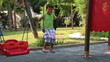 Little boy playing on a swing
