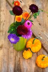 Herbstliche Dekoration mit Dahlien und Kürbissen