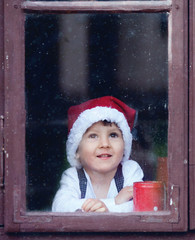 Adorable boy, looking through window, waiting for Santa
