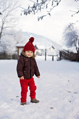 Portrait of child in brown jacket and red knitted hat and red tr