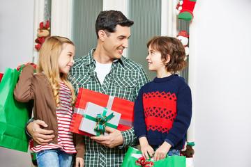 Vater schaut Kinder mit Geschenken an Weihnachten an