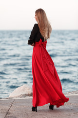 Sexy beauty woman in fluttering red dress. Fashion woman