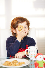 Junge hält Chocolate Chip Cookie an Weihnachten