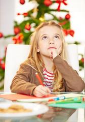 Kind schreibt Wunschzettel an Weihnachten