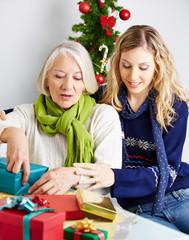 Frau hilft Seniorin beim Verpacken von Geschenken