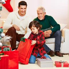 Junge packt Geschenke aus an Weihnachten