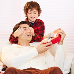 Sohn hält Vater Augen zu an Weihnachten