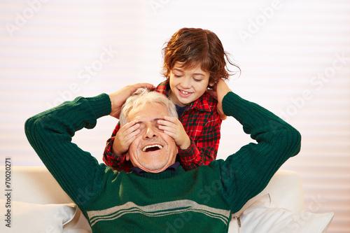 canvas print picture Kind hält seinem Opa die Augen zu