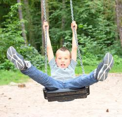 Hilarious boy have a fun on a garden swing.