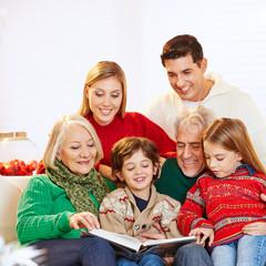 Familie in drei Generationen liest Buch zu Weihnachten