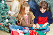 Mädchen und Junge packen Geschenke aus zu Weihnachten