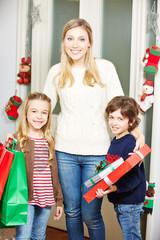 Mutter mit Tochter und Sohn tragen Geschenke an Weihnachten