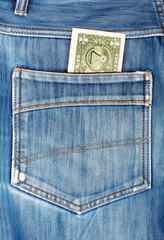 One dollar bill sticking in the back pocket of denim blue jeans