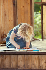 Little girl drawing with colored pencils on a country house wood