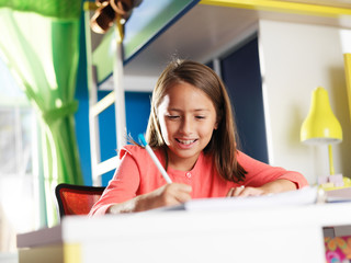 happy little girl doing homework in bedroom