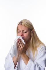 Blondine niest in ein Taschentuch