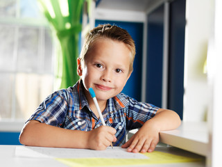 enthusiastic little boy doing homework