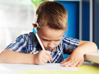 little boy working very hard on homework