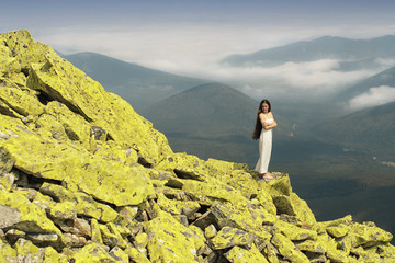 Sensual young woman standing on rocks in the mountains