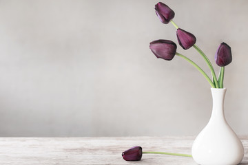 tulips in white vase on wooden table