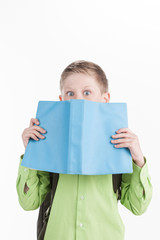 Portrait of little schoolboy with book on white background.