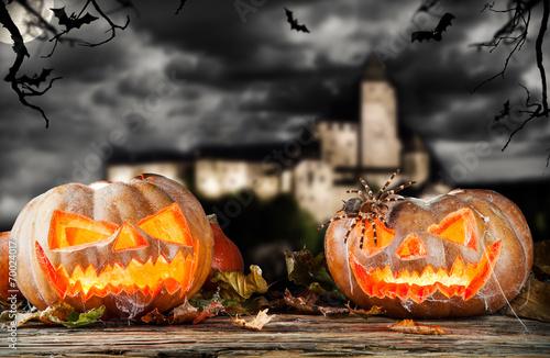 Leinwandbild Motiv Halloween pumpkins on wood with dark background