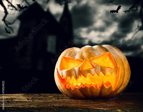 Leinwandbild Motiv Halloween pumpkin on wood with dark background