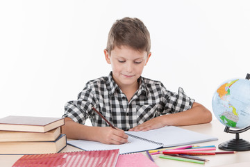 cute boy sitting at table and writing.