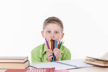cute boy sitting at table and holding colorful pencils.