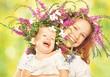happy daughter hugging mother in wreaths of summer flowers