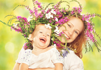 happy daughter hugging mother in wreaths of summer flowers