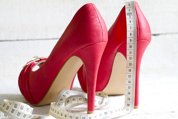 Closeup of high heel red woman shoes with centimeter concept