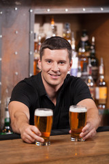 Bartender serving two glasses of beer.