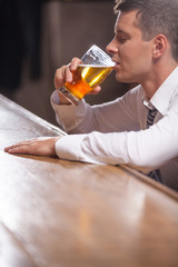 Lonely young man drinking alone at the pub.