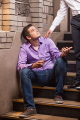 Handsome young man talking to man sitting on stairs.