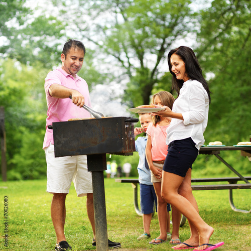 Fotobehang Picknick dad dishing out cooked food at family cookout
