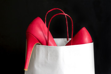 High heels red shoes in shopping bag against black