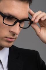 man wearing black glasses on grey background.