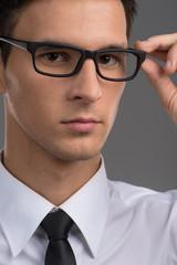 man wearing black tie on grey background.