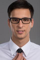 man holding black tie on grey background.