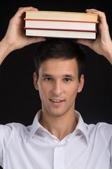 man holding books on black background.